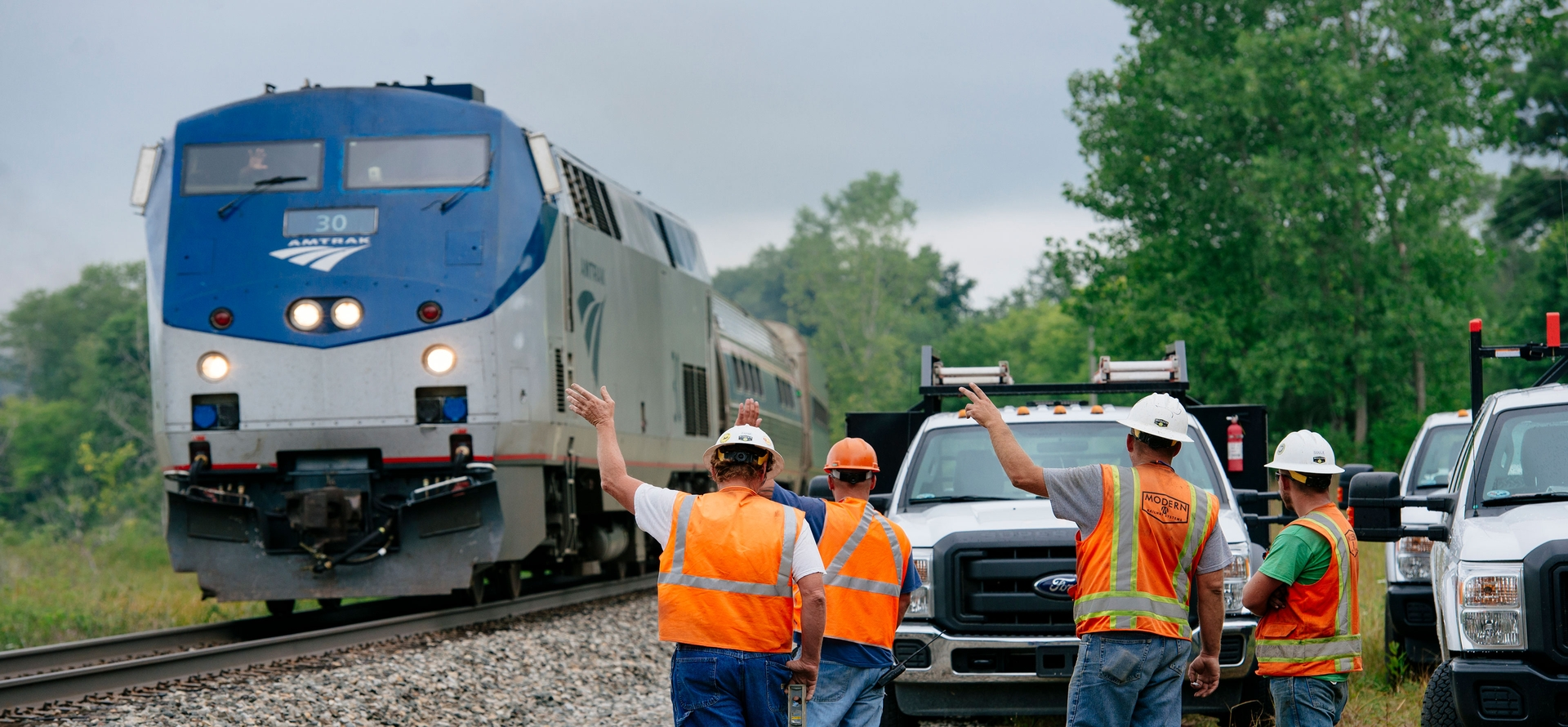 A group of workers wave at a departing train.