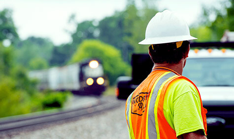 A worker in a safety vest watches a train approaching.